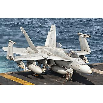 A US Navy FA-18C Hornet tied down on the flight deck of aircraft carrier USS Nimitz Poster Print
